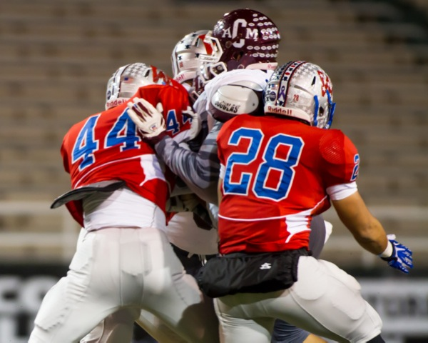 Players from Westlake and College Station's A&M Consolidated High School collide on the playing field