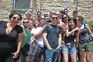 QueerBomb Collective & Friends: (l-r, front row) Risa Puleo, Matt Korn, Silky Shoemaker, d.king, Tamicka Phillips, Brett Hornsby, Paul Soileau, Melissa Smith, Beth Schindler, Raven Hinojosa; (l-r, back row) Joanna Labow, Kate Messer, Joe Sanchez, Bobby Johns (derby hat), Sym Prole, and Albert Dixon