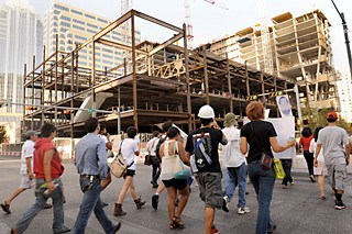 Workers and protesters walk toward White Lodging's construction site in August.