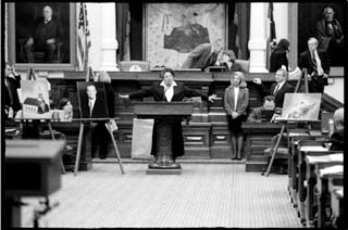 Rep. Senfronia Thompson, D-Houston, the House sponsor of the James Byrd Jr. hate crimes bill, addresses state representatives shortly before they approved the measure. An oversized photograph of Rep. Wayne Christian, who opposed the bill, rests on an easel to Thompson's right. Christian represents the town of Jasper, where Byrd, an African-American, was dragged to death behind a truck driven by three white men.