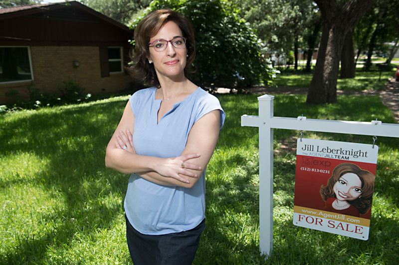 Woman looks determined while standing next to real estate sign in front of home