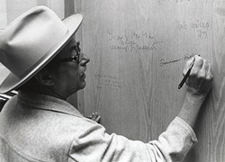 Tennessee Williams signs the authors' door during a visit to the Ransom Center in 1973.