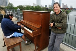 Artist/piano technician Johnny Walker and passerby Francisco Chavez playing the piano at the Play Me, I'm Yours project on the Pfluger Pedestrian Bridge