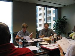 CELOC board members Anne Smalling and Wayne Hollingsworth study documents at the board's first public meeting July 16.