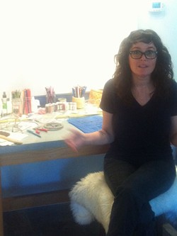 Ewalt, in front of her work table, explains her drawing process.
