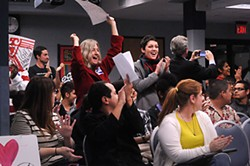 Members of the crowd celebrate as the vote to approve a charter at Travis Heights Elementary passed.