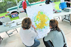 Two Austinites check out a map of the city at a rally in support of 10-1 districting in October 2012.