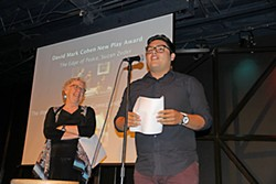 Recent UT graduate Isaac Gomez accepts the David Mark Cohen New Play Award for <i>The Women of Juarez</i>, which he co-wrote with Bianca Sulaica. Looking on is Gomez's mentor, retiring UT playwriting professor Suzan Zeder, who shared the award for <i>The Edge of Peace</i>, the conclusion to her Ware Trilogy. Gomez was also one of five recipients this year of the W.H. Deacon Crain Award for Outstanding Student Work.