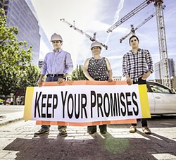 L-R: Former construction worker Christian Hurta­do, WDP member and construction worker Juana Silva, and WDP volunteer Jorge Ramir­ez, across the street from the Marriott project on Congress, with a sign calling on White Lodging to keep its promise on wages.