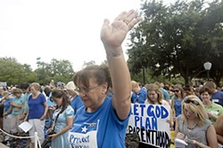 Dressed in blue, hundreds of pro-life supporters pray during a rally outside the Capitol Tuesday night; meanwhile, an orange-attired, pro-choice crowd marched down Congress. See SB 1/HB 2: How a Lie Becomes a Law, p.12.