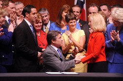 Gov. Rick Perry hands a pen he used to sign HB 2 into law to Rep. Jodie Laubenberg, House sponsor of the bill.