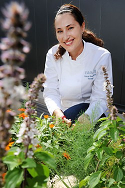 Valerie Broussard tends to future ingredients in the Trace herb garden on the roof of the W Hotel.