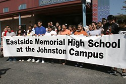 Students hold a banner in a ceremony changing the name Johnston High School to Eastside Memorial High School