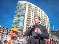 The Rev. Jim Rigby speaks at a workers' protest at Gables Park Tower.