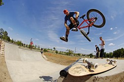 Taj Mihelich performs a tailwhip on the new miniramp at Patterson Park, across from Mueller. The ramp, open to skateboard and BMX riders, is part of a long-range effort to provide a citywide network of public skateboarding facilities. The Austin Public Skatepark Action Committee completed the Patterson ramp project with donated funds and volunteer construction labor.