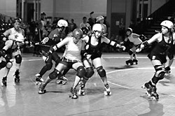Lucille Brawl (center) blocks while Olivia Shootin' John (left) takes a skirt-whip off Rice Rocket (3e8) as the Texas Rollergirls' travel team, the Texecutioners, faces the Oly Rollers at the WFTDA 2009 finals in Philadelphia.