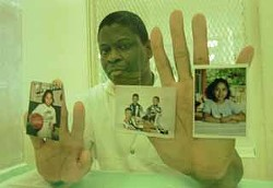 Rodney Reed holding photos of his children