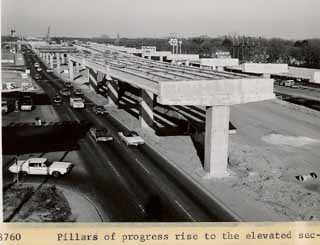 Pillars of progress rise over what was then North Austin -- right by Hancock Center and today's <i>Chronicle</i> offices -- as work begins in the mid-1960s on the I-35 upper deck (completed in 1975). In TxDOT's plans for the I-35 of tomorrow, the upper deck comes down (except for elevated HOV lanes) and the freeway widens, taking out both the Sears auto shop (far left) and the now-moved Academy Sporting Goods (right).
