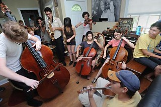 Crammed into the living room and spilling into the hall and kitchen are 14 classical musicians, their instruments, and their cases. The strings are huddled by the front door; percussion and horns stand over the couch.