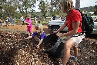 Katherine Beisner and daughters Ruby and June pitch in at a 2009 volunteer event.