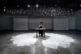 Sew Calm Under the Circumstances: Beili Liu at work in/on <i>The Mending Project</i> (2011), metal scissors and mixed media.