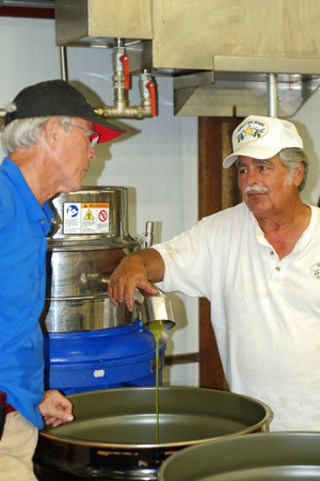 Jerry Farrell (r) and Jim Henry (l) press Farrell's 2010 olive oil.