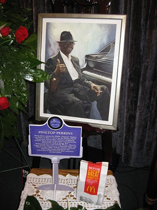 Flanking Pinetop's casket, a portrait by Diane Russell, his marker from the Blues Highway, and his ever-present McDonald's bag