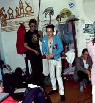 Strummer and Ely (kneeling) backstage at the Dillo