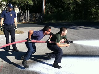 Mark Brandon Dominguez (r), learning how to use a fire hose, guided by Lt. Eddie Dominguez (no relation)