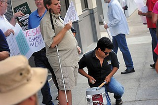 Dave Cortez beats a bucket-drum outside Blue Sage Capital, which his group and union reps claim is tied to union-busting activities.