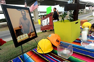 A shrine of hard hats, candles, and a photo of José Lainez, a fallen construction worker, sits on a table at a July 11 vigil near the U.S. 183 construction site where Lainez died June 15.  The Workers Defense Project, which sponsored the vigil, says the father of five died of heat exhaustion because adequate water and rest breaks were not provided at the job site.