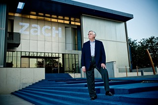 Bruce McCann, immediate past president of the Zach Theatre board, stands at the entrance to the building to which he devoted himself, making sure it was built as designed, on time and on budget.