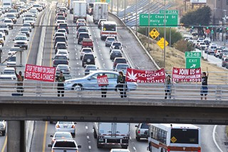 Members of the Texas Hemp Campaign proudly display their support for the legalization of marijuana by dropping banners from the 11th Street bridge on the last Friday of the month.