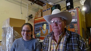 Amy Cartwright (l) gives Independence Brewery's spent grain to great-grandfather Calvin Jechow (r), who feeds it to his free range chickens and turkeys.