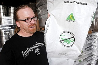 Rob Cartwright shows off the dinosaur label, which means no fossil fuels were used to produce these malts.