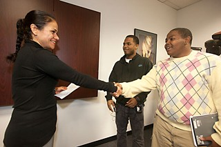 Texas Education Agency Chief Deputy Commissioner Lizzette Reynolds (l) accepts a letter from Eastside Memorial High School students Julian Medrano (c) and Elijah Cofield (r); it asks Commissioner Michael Williams to visit the school to discuss its potential closure or takeover by another entity.