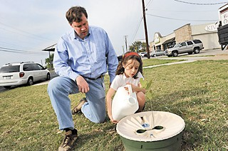 Steven Zettner and his daughter Mattie water trees they planted along Burnet Road near Koenig.