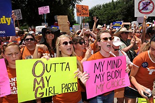 Women hoist signs of opposition to proposed abortion legislation.