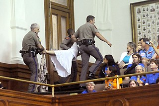 DPS troopers carry, not so delicately, a protester out of the Senate gallery during last week's debate on legislation that further restricts women's ability to obtain abortion procedures. See The Making of a Movement for more.