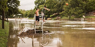 Two men throw a pumpkin into Barton Springs Swimming Pool from a marooned lifeguard tower, after weekend flood waters forced the pool's closure and prompted organizers of the Austin City Limits Music Festival to cancel the last day of the event due to swampy conditions at nearby Zilker Park.