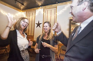 Council Member Laura Morrison and Travis County Republican Party Vice Chair Roger Borgelt exchange high-fives at the housing campaign's election watch party at Scholz Garten, while HousingWorks' Mandy De Mayo looks on.