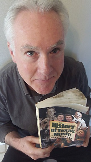 Gary Hartman holds a waterlogged copy of his <i>History of Texas Music</i>.
