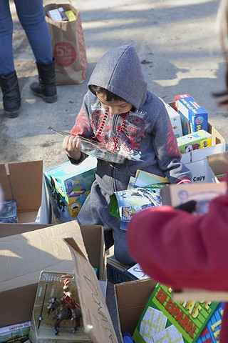 A child opens gifts at a holiday party for the victims of the Onion Creek and Yarrabee Bend flooding Halloween night.