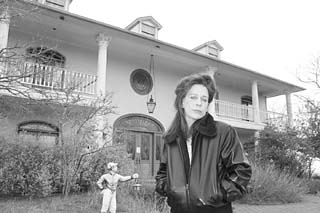 Melinda Ballard in front of her 12,000-square-foot replica of Tara, the <i>Gone With the Wind</i> mansion, in Dripping Springs. The house is now completely uninhabitable, destroyed by mold.