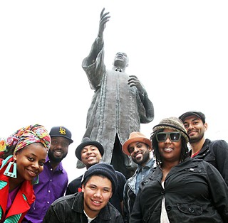 All Rise: (l-r) Tiger Lily, Bavu Blakes, Da'Shade Moonbeam (back), DJ Charlie (front), Chaka Mpeanaji, Queen Deelah, and DJ Chorizo Funk at UT's MLK statue