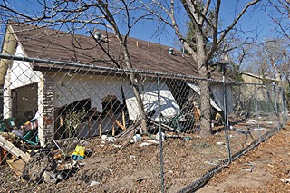 A familiar sight in the Onion Creek neighborhood – a home destroyed by the flood, surrounded by a chain link fence, and waiting to be demolished.