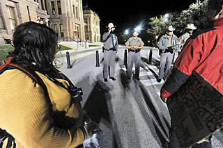 A Texas Department of Public Safety trooper videotapes while another trooper asks Occupy Austin participants to leave the state Capitol on Nov. 27.