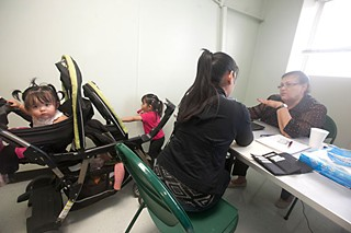 Isabelle Rosenzweig signs up Renalda Hernandez and her daughters Kelsey, 2, and Geraldine, 10 months, at the Montopolis Recreation Center, at a March 20 outreach event hosted by Enroll America/Get Covered America.
