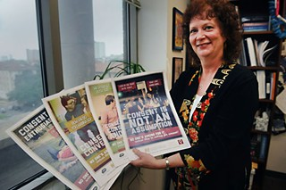 Jane Bost, associate director of Pre­ven­tion and Outreach Services at UT's Counseling and Mental Health Center, displays posters designed to educate students about the necessity of consent in sexual relationships.