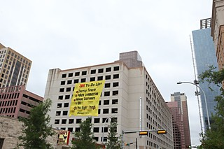 A mock Post-it note hangs from a Downtown parking garage Tuesday as part of several protest actions staged by ForestEthics and other enviro groups as 3M shareholders met at the Convention Center.